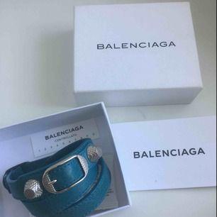 Blått Balenciaga armband med silvriga detaljer. Kommer med original låda och kort. Inga tydliga slitningar eller skador. Storlek M