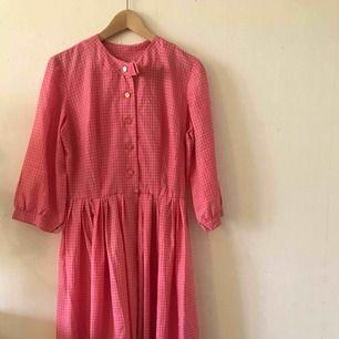Mycket vacker klänning i 50-tals stil i en varm, rosa färg. Stor vidd på kjol. Knappar framtill.  Storlek: Passar 38/40. Skick: Nästan oanvänd.  Kan skicka mot frakt i PostNords blå färdigfrankerade kuvert.