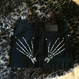 Supercool svart minikjol i jeansmaterial, med ballaste trycket där bak! Tyvärr för liten för mig. Aldrig använd men köpt för många år sen så tvivlar på att den går att få tag på ny.
