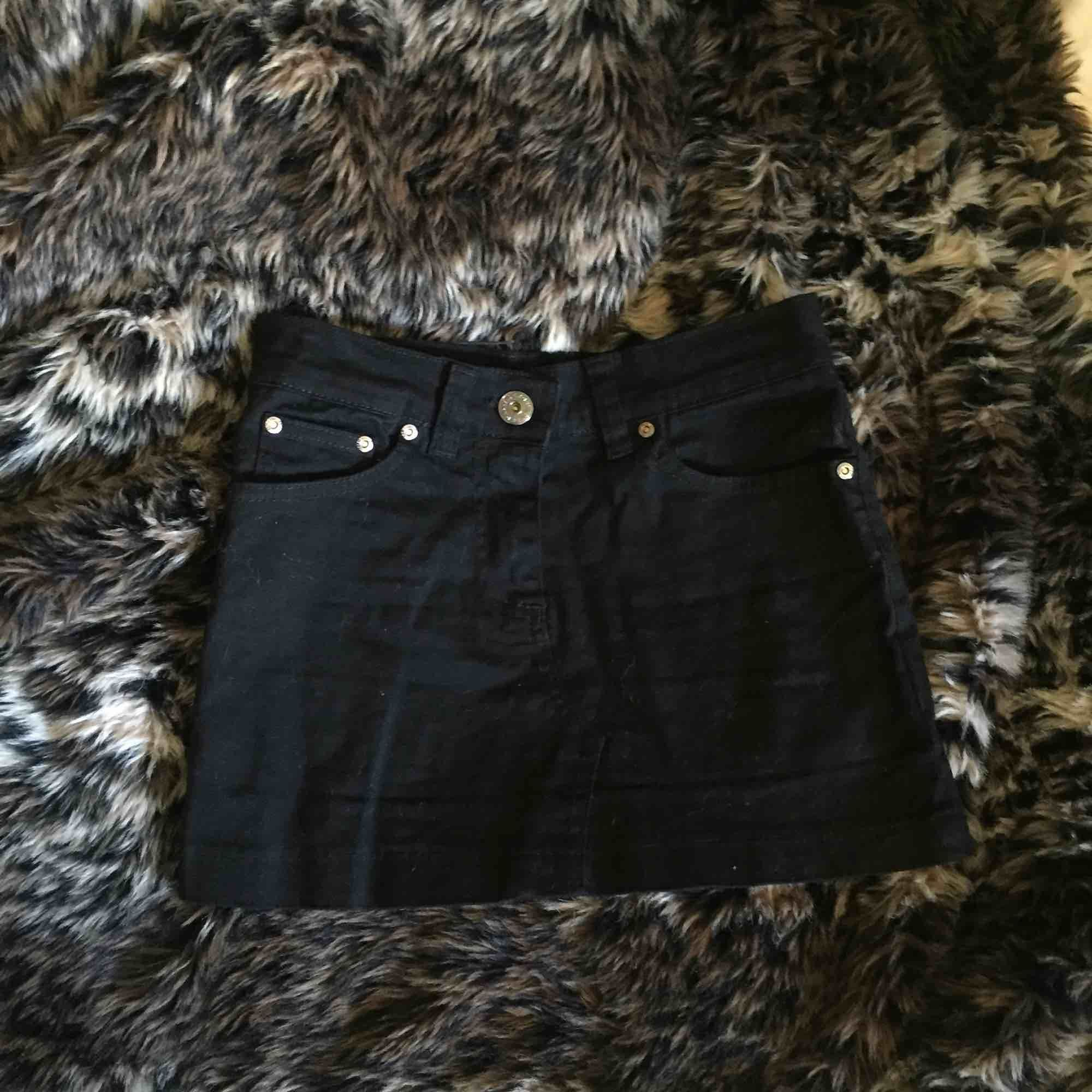 Supercool svart minikjol i jeansmaterial, med ballaste trycket där bak! Tyvärr för liten för mig. Aldrig använd men köpt för många år sen så tvivlar på att den går att få tag på ny.. Kjolar.