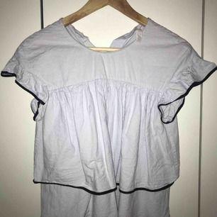 Strl XS - ljusblå med svarta kontraster  - tre knappar bak på tröjan (se bild 3) - perfekt till sommaren!! - fint skick då den bara använts fåtal gånger