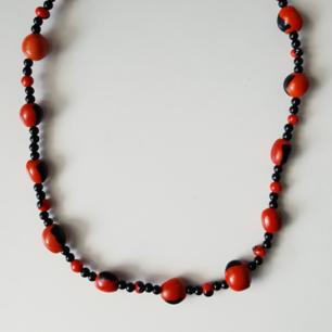 Halsband med svarta och orangea träpärlor. Fraktkostnaden blir 9kr.