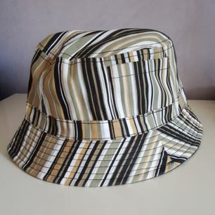 Randig bucket hat i onesize som passar de flesta. Har fickor på sidorna. Fraktkostnaden blir 36kr.