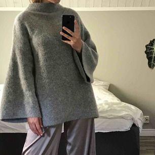 Stor stickad tröja, hög i halsen och vida ärmar.(blandning av mohair, ull, polyester & polyamid)