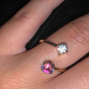 """Cool ring i guldfärg med två stenar i. En silver och en """"regnbåge"""". Storleken går att bestämma lite själv då man kan göra avståndet mellan stenarna större eller mindre!"""