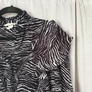 Frän skjorta i zebraliknande mönster med volanger. Två volanger frampå på varje sida och en liten ut längs ärmen! Frakt på 25kr tillkommer🦓