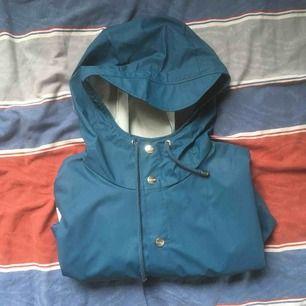 Blå regnjacka från Rains aldrig använd. Nypris 749:-  FRI FRAKT.