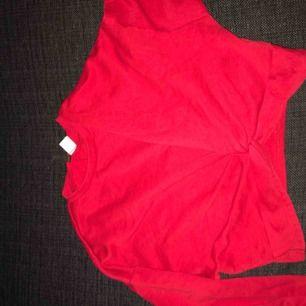 En croppad röd tröja med omlott-knytning vid midjan  Använd en gång