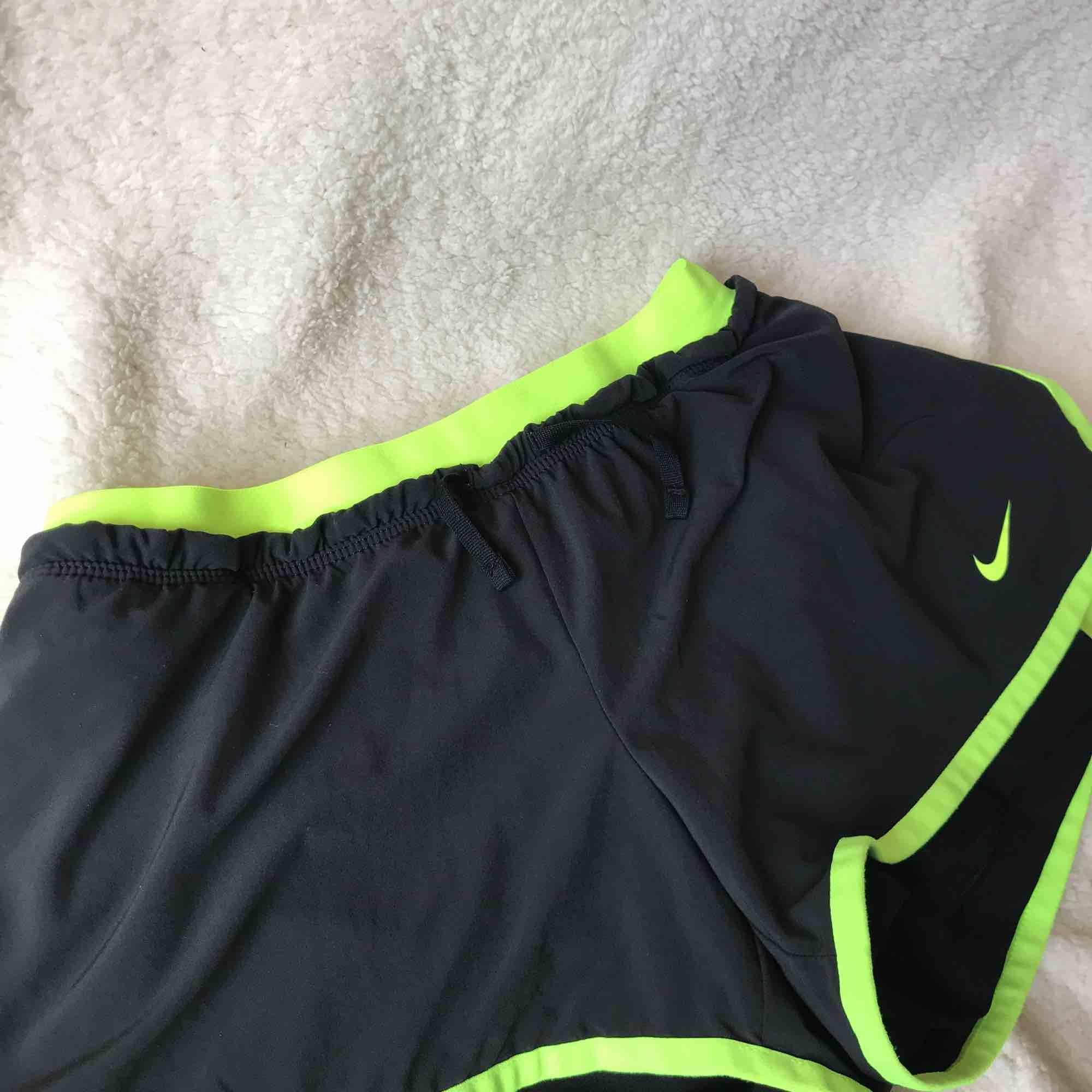 Svarta Nike shorts med neon färg i rem.  Har haft på mig den några gånger men de är i en väldig god skick.  Pris kan förhandlas. . Shorts.
