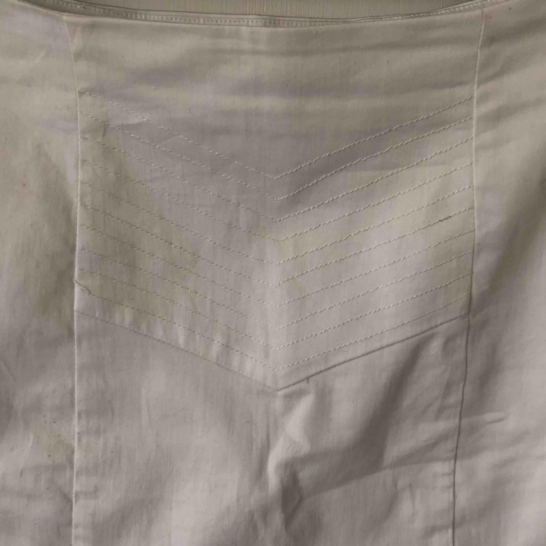 Vit kjol med volang på baksidan och broderat mönster på framsidan. Köparen står för frakten🌸. Kjolar.