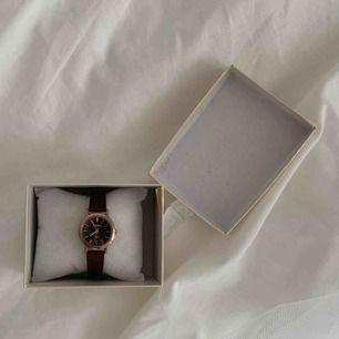 Stilren och trendig unisex-klocka. Klockan har en svart urtavla, brunt band och guldfärgad boett.   Betalning görs via swish :) Fri frakt.