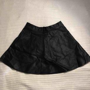 Svart fake-läder kjol med dragkedja på baksidan. Storlek 152/XS-S. Extremt snygg men säljer då den är alldeles för liten för mig.💜