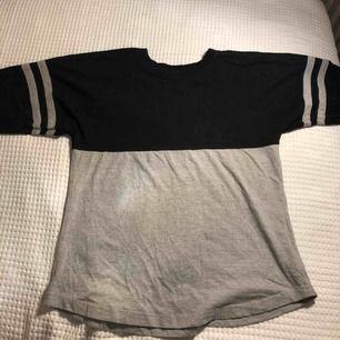 """Svart och grå typ basket tröja. Långärmad med vit glittrig text """"demons"""" på ryggen. Gråa streck på överarmen."""