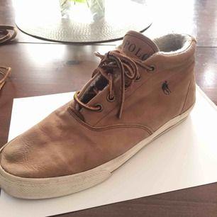 Ralph Lauren höga sneakers med lite foder inuti. Nypris 1399. Storlek 41, 26 cm passar vissa 42:or. Bruna vanliga skosnören medföljer. Material släpper lite längst fram på skon(3). Fler bilder eller frågor bara kontakta :)