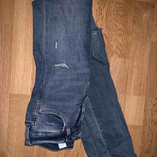 Blåa slitna jeans