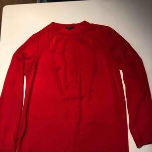 Röd blus med cutout detalj upptill och dragkedja framtill. Använd ett fåtal gånger och i nyskick. Hämtas i Malmö eller skickas mot frakt.