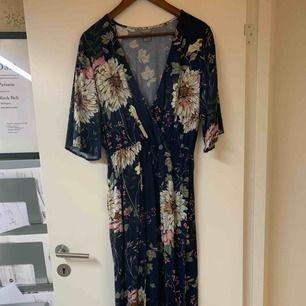 Långklänning med blommigt mönster. Knapp framtill vid urringningen. Använd en gång.
