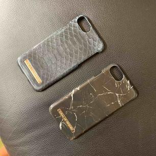 Mobilskal till iPhone 6s från Ideal of Sweden. 100sek styck. En med reptilmönster i grönblått och ett med svart marmormönster.