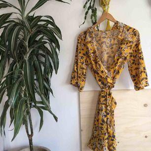 Superfin gul blommig omlottklänning med knyt från Monki, fint skick. Slutsåld förra sommaren.