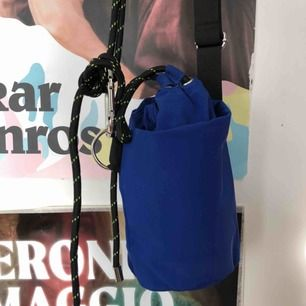 """Väska från weekday, en modell i form av en """"hink"""". Cool väska i en kornblå färg med straps och häftiga detaljer."""