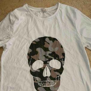 En t-shirt från River island med en döskalle på Inte använd på ca 1 år men i lika fint skick som när jag köpte den Storlek 10 vilket motsvarar stl 36 i Sverige, den är lite oversize men inte jätte