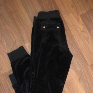 Svarta mjukisbyxor från juicy couture med svart glittrig text längst benet