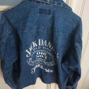 Jeansskjorta/jacka med Jack Daniels tryck på ryggen. Köpt second hand. verkar vara någon som klippt/sytt innan men inte gjort ett bra jobb. Sömmen nertill lite sne men går ju att fixa till :p