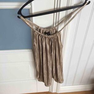 Guldigt plisserat linne från hm med högre halsringning. Sparsamt använt.