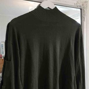 Grön tröja med krage och knytsnören nedtill. Strl M. Frakten står köparen för.