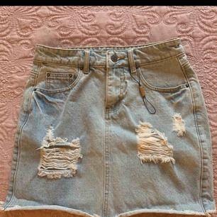 Ljusblå jeanskjol med slitningar från Nelly.com. Aldrig använd. Den har kvar en tag, dock har själva lappen ramlat av så därför är det bara ett snöre kvar! Super snygg men aldrig kommit till användning 💘