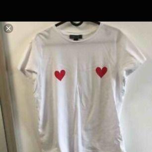 Vit T-shirt med två röda hjärtan som tryck. Tröjan är från primark och är i storlek XS/S. Använd 1-2 gånger, en gång ute och en gång hemma så skicket är som nytt. Helt felfri!