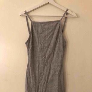 Grå ribbad klänning i storlek 34. Stretchig och super skön, väldigt skrynklig då den legat i en garderob. Går lägre ner på ryggen som ni kan se på bilderna. Använd 2 gånger, ena gången endast hemma!