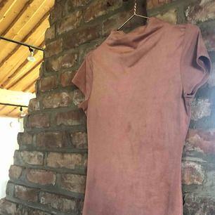 Detta är en knälång klänning i mockaimitation som har lite högre krage. Klänningen är superfin men den har tyvärr blivit liggande hemma i garderoben. Som ny, och kan användas vid lite mer vanliga tillfällen men även uppklätt!   Frakt tillkommer