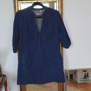 Supersöt jeansklänning med snörurringning och fickor. Mycket gott skick och 90talsstuck. Lite skrynklig men det går att stryka enkelt :-) 100kr inklusive frakt🌻