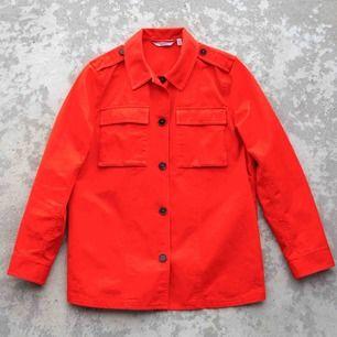 Knallig orangeröd jacka i tjockare bomullsmaterial. Endast använd ett fåtal gånger. Stl 36 men passar även 38. Hämtas i Stockholm annars tillkommer frakt.