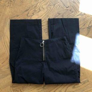 Marinblå högmidjade byxor i kostymbyxmaterial med kortare längd och utsvängda. Skickar gärna bild efter förfrågan!