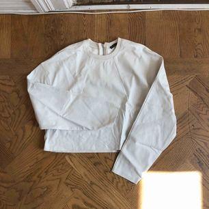 Vit tröja i skinnimmitation, färgen går i en lite mörkare ton! En aning croppad.