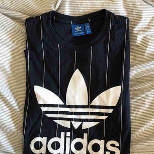 Adidas t- shirt blå med smala vita ränder med stort tryck på bröstet, använd ett fåtal gånger  (köparen står för frakt)