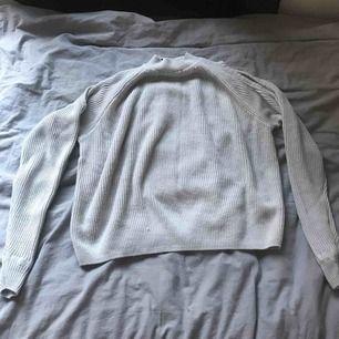 Grå stickad tröja från H&M, ish halterneck. Plus två styckna hål i varje arm