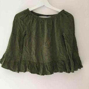Militärgrön tröja med volanger. Använd men i bra skick! (Lite skrynklig men hade inte möjlighet att stryka den)