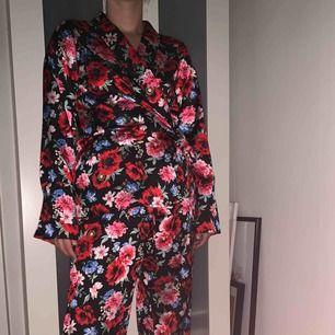 Matchande blommigt set med byxa och kimono/kavaj i silkigt material. Använt fåtal gånger, men bra skick! Storlek 42 men passar alla under det också då man kan knyta. Jag har själv 38/40 och passar mig perfekt.