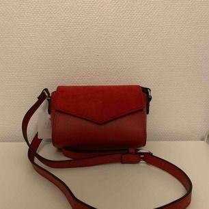 Liten, röd axelremsväska från New Look. Aldrig använd, prislapp fortfarande på. 🥰