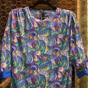 Påfågelliknande hypnotiskt mönster i denna retroklänning med axelvaddar och lager av kjol nedtill!