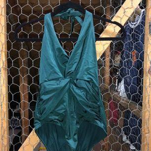 Skogsgrön baddräkt (inte turkos som bilderna visar) med låg rygg och knytning i nacken, oanvänt skick!