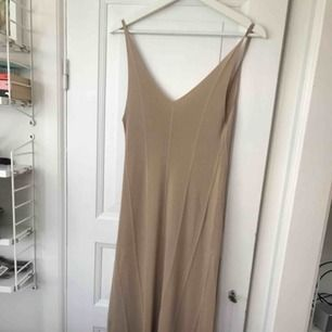 Finstickad klänning från hm beige. Lite urringad i ryggen. Slutar ca 10 cm ovanför ankeln på mig som är 163. Fint skick aldrig använd.