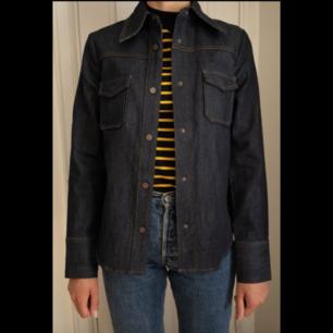 Jeansskjorta i rådenim med 70-talskrage som även kan användas som jacka. Strl 34 / XS.   Endast provad, mycket fint skick!
