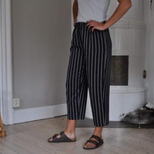 Svarta breda vintage byxor, med röda och vita ränder. Storlek small. Har resår i midjan!💛
