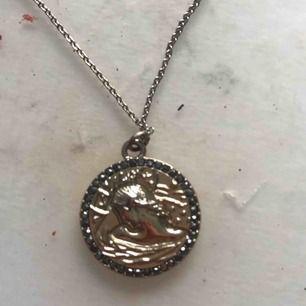 Guldigt halsband med gröna diamanter på själva berlocken
