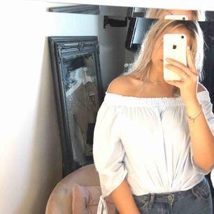 En randig off-shoulder tröja med små söta knutar på armen.