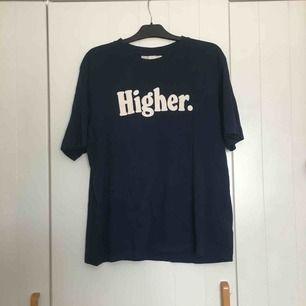 """Mörkblå tisha från HM med trycket """"Higher."""" på. Relativt oanvänd och köpt så den ska sitta snyggt oversize från herravdelningen!"""